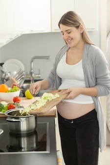 Porträt einer lächelnden schwangeren frau, die gemüse in die suppe einsetzt