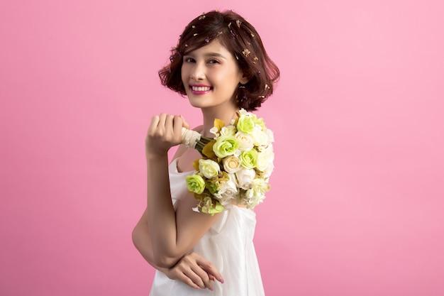 Porträt einer lächelnden spielerischen netten frau, die blumen lokalisiert auf rosa hält