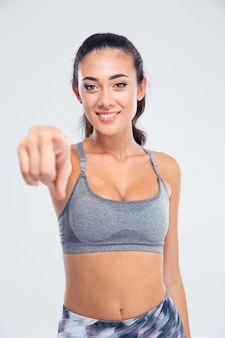 Porträt einer lächelnden sportfrau, die finger an der front lokalisiert auf einer weißen wand zeigt