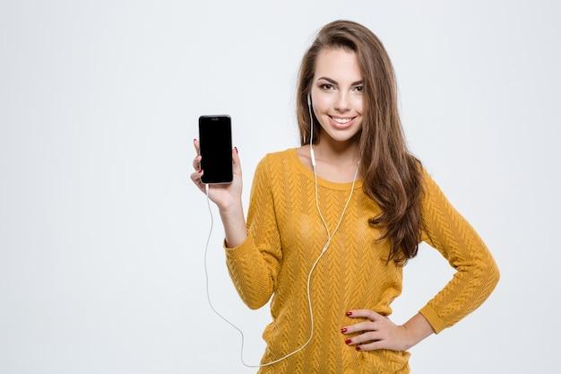 Porträt einer lächelnden süßen frau, die einen leeren smartphone-bildschirm isoliert auf weißem hintergrund zeigt
