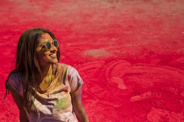Porträt einer lächelnden tragenden sonnenbrille der jungen frau, die in holi farbe verwirrt