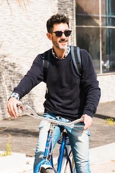 Porträt einer lächelnden tragenden sonnenbrille des mannes, die auf sein fahrrad fährt