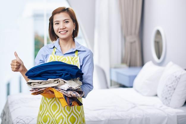 Porträt einer lächelnden vietnamesischen hausfrau, die einen stapel gefalteter kleidung hält, bügelt sie und zeigt daumen hoch