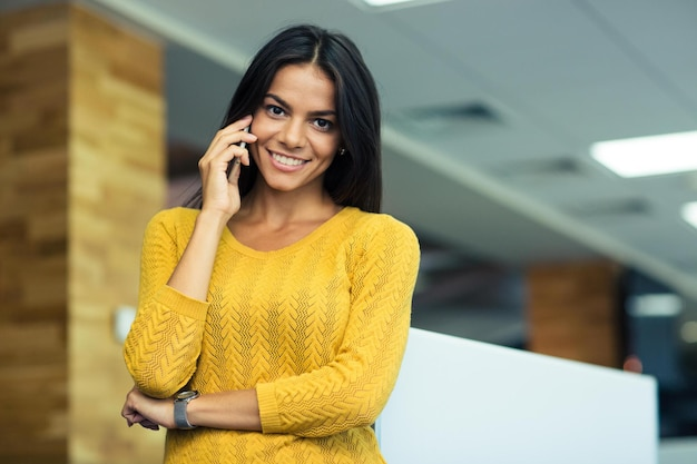 Porträt einer lächelnden zufälligen geschäftsfrau, die im büro am telefon spricht. blick in die kamera