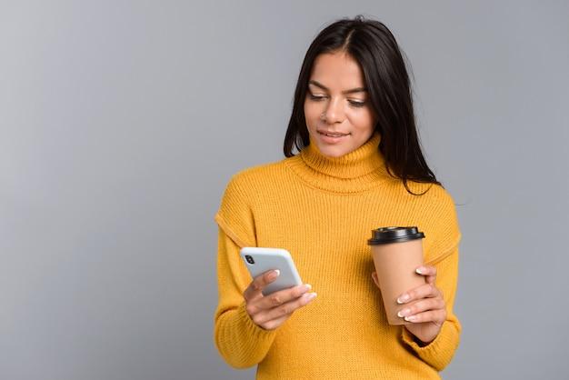 Porträt einer lässigen jungen frau lokalisiert über graue wand, kaffee zum mitnehmen haltend, unter verwendung des mobiltelefons
