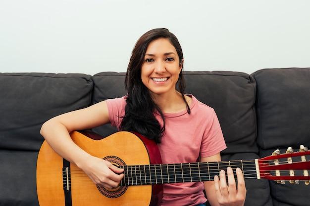 Porträt einer lateinamerikanischen frau, die gitarre im wohnzimmer sitzt, das auf der couch sitzt