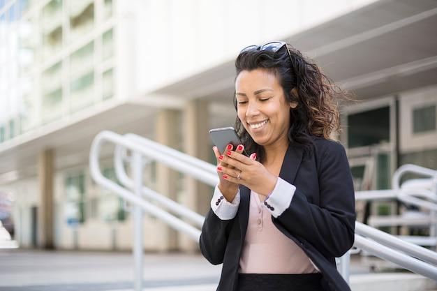 Porträt einer lateinamerikanischen unternehmerin, die eine sprachnachricht auf ihrem smartphone aufzeichnet. sie trägt formelle kleidung und ist draußen.