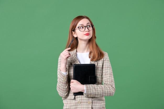 Porträt einer lehrerin im anzug mit notizblock und stift auf grün