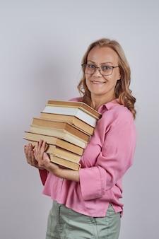 Porträt einer lehrerin mit brille, die einen stapel bücher isoliert hält