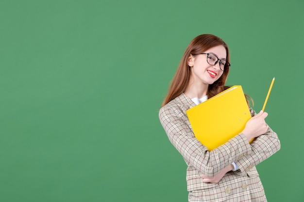 Porträt einer lehrerin posiert mit gelber datei und bleistift glücklich lächelnd auf grün