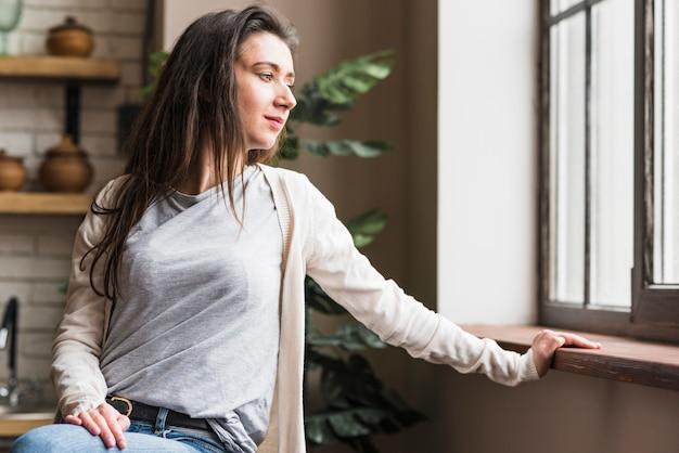 Porträt einer lesbischen frau, die fenster betrachtet