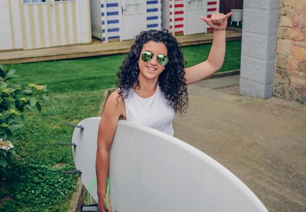 Porträt einer lockigen brünetten surferin mit weißem oberteil und sonnenbrille, die mit einem surfbrett geht