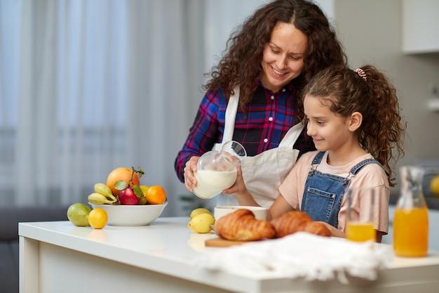 Porträt einer lockigen mutter gießt ihre süße tochtermilch in eine schüssel mit getreide. zeit fürs frühstück