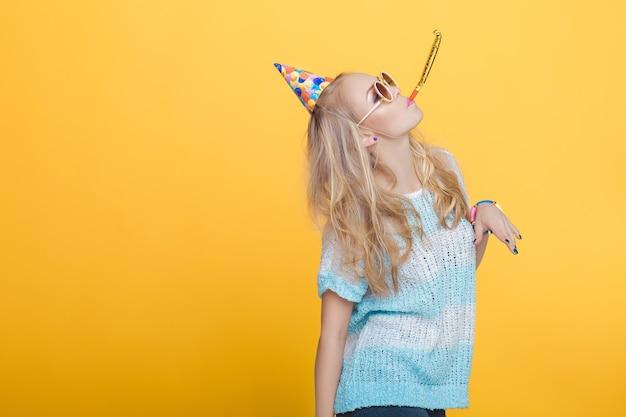 Porträt einer lustigen blonden frau in geburtstagshut und blauem hemd auf gelbem hintergrund, feier und party