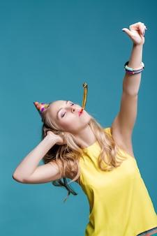 Porträt einer lustigen blonden frau mit geburtstagshut und gelbem hemd auf blauem hintergrund, feier und party