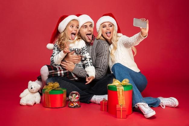 Porträt einer lustigen familie mit einem kind in voller länge