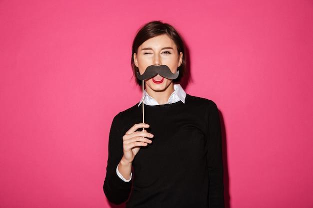 Porträt einer lustigen jungen geschäftsfrau mit dem papierschnurrbart