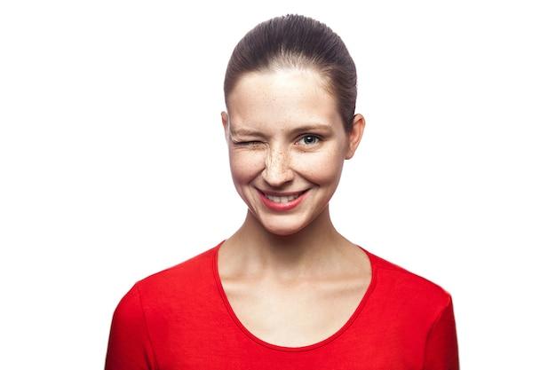 Porträt einer lustigen, positiv zwinkernden frau im roten t-shirt mit sommersprossen, die in die kamera schaut