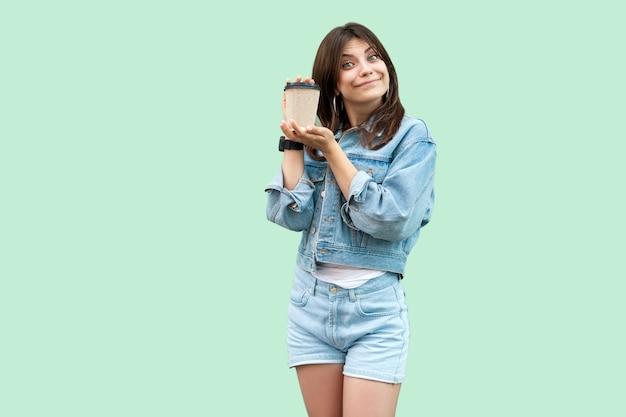 Porträt einer lustigen schönen jungen brünetten frau im lässigen denim-stil, die eine einwegschale heißes getränk steht und hält und in die kamera schaut. indoor-studioaufnahme, auf grünem hintergrund isoliert.