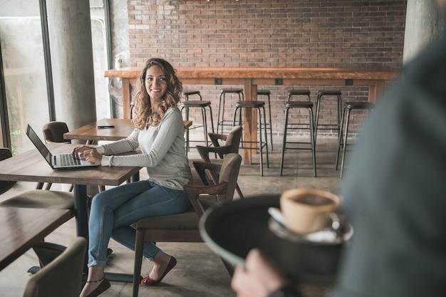 Porträt einer männlichen kellnerin, die einer kundin kaffee serviert