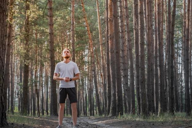 Porträt einer männlichen person, die in einem kiefernwald an einem sonnigen tag steht