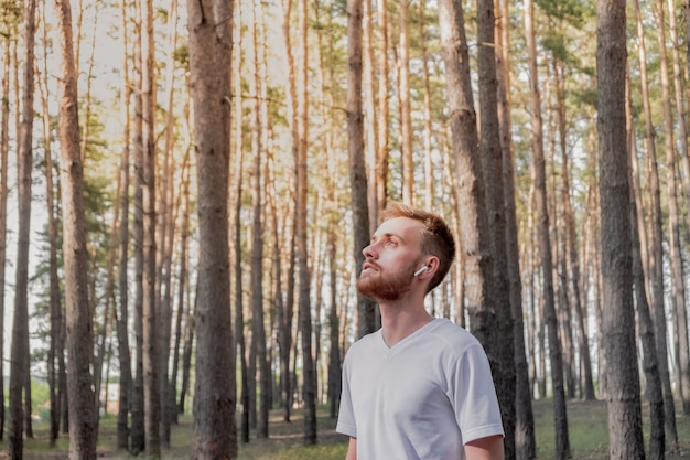 Porträt einer männlichen person mit den drahtlosen kopfhörern, die in einem kiefernwald an einem sonnigen tag stehen