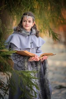 Porträt einer märchenelfe mit einem magischen buch in ihren händen vor dem hintergrund der winternatur