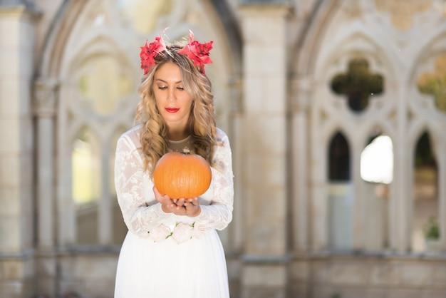 Porträt einer märchenkönigin, die einen kürbis hält