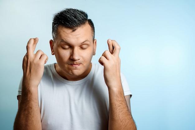 Porträt einer mannnahaufnahme, gekreuzte finger, hoffnung, viel glück.