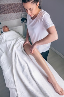 Porträt einer massagetherapeutin, die lymphdrainagemassage an den beinen einer jungen frau in einem klinischen zentrum durchführt. medizin-, gesundheits- und schönheitskonzept.