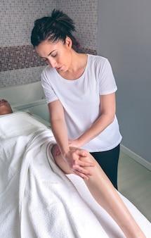 Porträt einer massagetherapeutin, die lymphdrainagemassage an den beinen einer jungen frau in einem klinischen zentrum macht. medizin-, gesundheits- und schönheitskonzept.