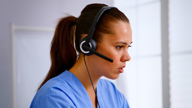Porträt einer medizinischen empfangsdame, die auf kopfhörer antwortet und dem patienten hilft, einen termin im krankenhaus zu vereinbaren. arzt im gesundheitswesen in medizinuniform, arzthelferin während der telemedizin-kommunikation