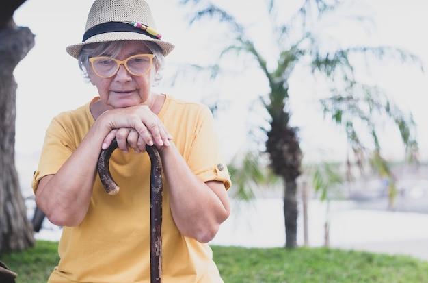 Porträt einer melancholischen seniorin, die unter rückenschmerzen leidet, die draußen auf dem stock sitzt