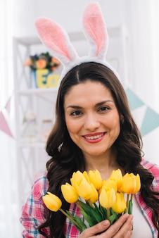 Porträt einer mittleren erwachsenen frau mit dem häschenohr auf ihrem kopf, der in der hand gelbe tulpen hält, die zur kamera schauen