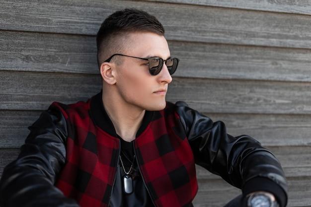 Porträt einer modernen hübschen trendigen jungen mann-hipster-sonnenbrille mit einer modischen frisur in einer stilvollen rot karierten jacke mit lederärmeln nahe einer holzwand