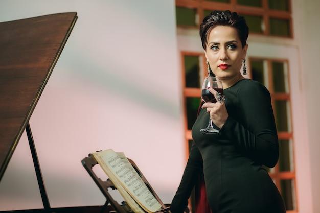 Porträt einer modischen und attraktiven frau, die neben dem klavier steht und weinglas hält