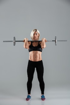 Porträt einer motivierten muskulösen erwachsenen sportlerin in voller länge