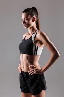Porträt einer motivierten schlanken fitnessfrau, die aufwirft