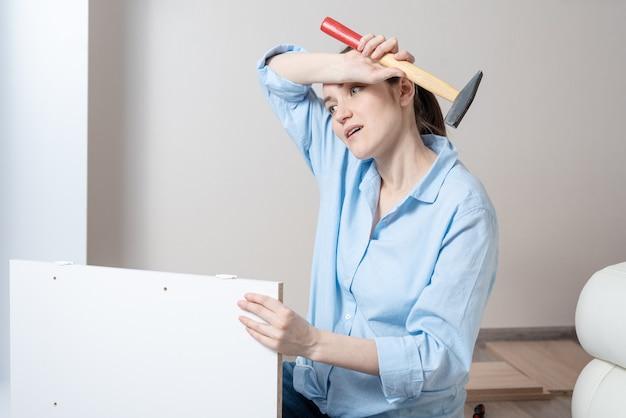 Porträt einer müden brunettefrau mit einem hammer in ihren händen, wischt ihre stirn mit schweiß ab