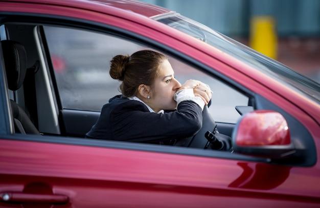 Porträt einer müden frau, die auto fährt und durch das fenster schaut