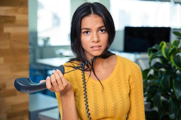 Porträt einer müden geschäftsfrau, die telefon im büro hält