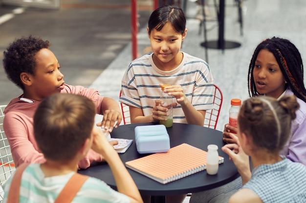 Porträt einer multiethnischen gruppe von kindern, die während des mittagessens in der modernen schule im freien am tisch sitzen