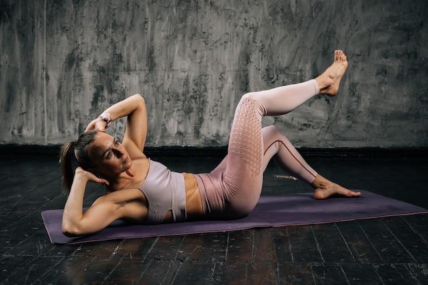 Porträt einer muskulösen jungen athletischen frau mit perfektem, schönem körper, die sportkleidung trägt und kreuzweise crunch-übungen macht, die auf der matte liegen. kaukasische eignungsfrau, die im studio mit dunklem hintergrund aufwirft.