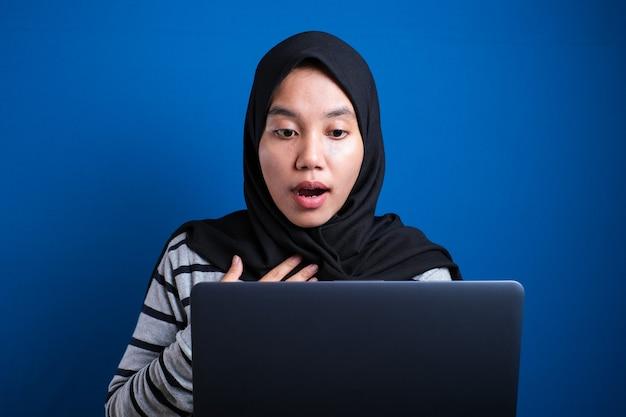 Porträt einer muslimischen geschäftsfrau mit hijab mit laptop mit schockierter, fassungsloser geste des gesichtsausdrucks, frau im büro