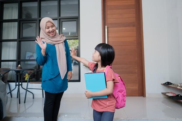 Porträt einer muslimischen mutter, die sich von ihrer tochter verabschiedet, bevor sie zur schule geht