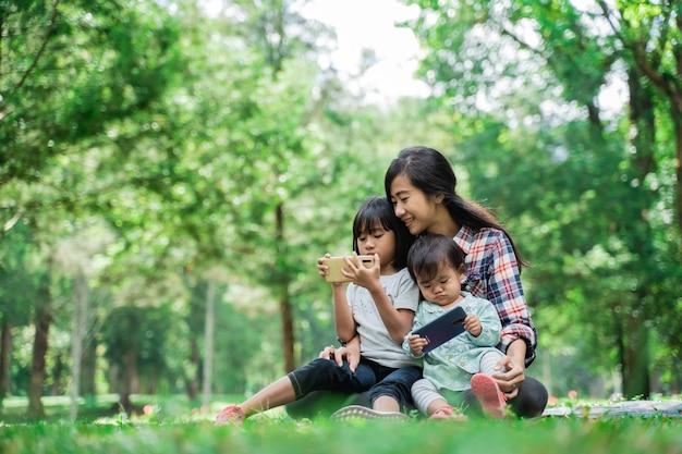 Porträt einer mutter, die ihre kinder begleitet, um im park handys zu spielen