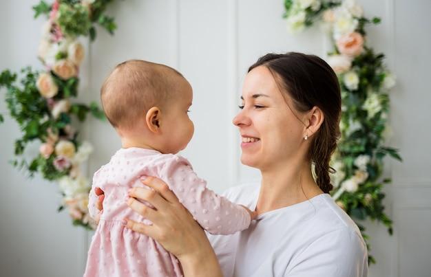 Porträt einer mutter, die mit einem baby auf einem weißen hintergrund mit einem blumenhintergrund spielt.