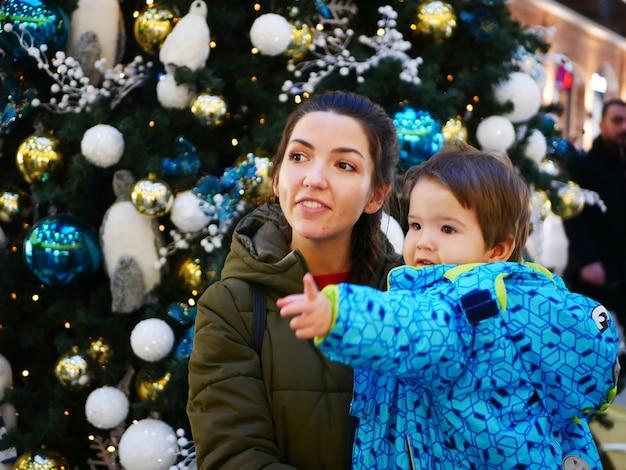 Porträt einer mutter mit einem kind nahe einem neujahrsbaum in der warmen kleidung