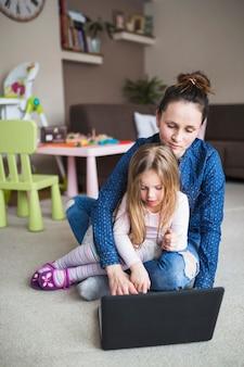 Porträt einer mutter mit ihrer tochter, die auf teppich unter verwendung des laptops sitzt