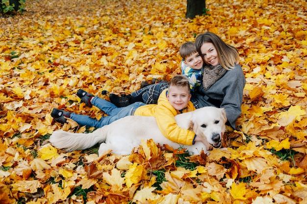 Porträt einer mutter mit zwei söhnen und einem hund in einem herbstpark